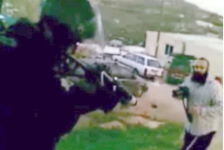 Policeman aims before firing at Havat Gilad.