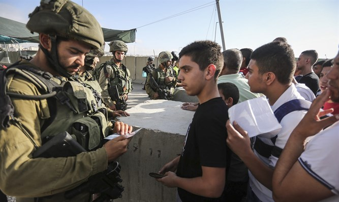 Israeli soldiers checking Palestinian IDs at the Qalandia checkpoint
