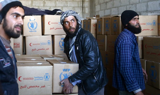 Man carries a box of supplies in the village of Otaya, eastern Ghouta, in Damascus