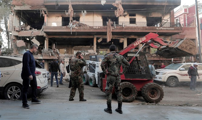 Syrian soldiers stand near damaged building in Mezzah